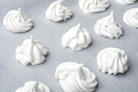 Whipped cream on baking paper. Meringue of the proteins and sugars. Step-by-step recipe for meringue cookies. Process of meringue preparation Stok Fotoğraf