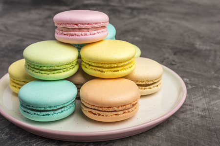 Sweet colorful macarons on the plate. Dark background