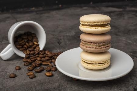 Delicious, cookies macarons on the plate. The taste of coffee and chocolate. Dark background Stock Photo