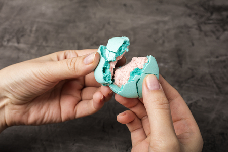 Tasty macaron is broken in half in female hands. Dark background
