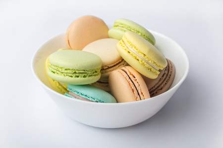 Colorful macarons in plate, on a Light background