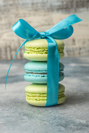 Delicious sweet colorful cookies macaron, macaroon with blue bow on a light background Standard-Bild - 124470955