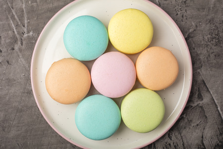 Sweet colorful macarons on the plate. Dark background. View from above