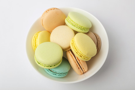 Colorful macarons in plate, on a Light background. View from above