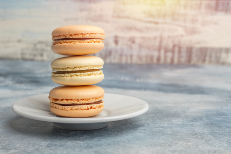Delicious, colorful cookies macarons on the plate. Light background