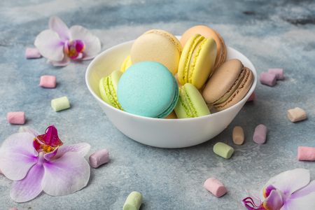 Colorful cookies macarons on the plate and airy marshmallows. Light background