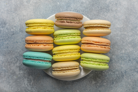 Delicious, colorful cookies macarons on the plate. Light background. View from above