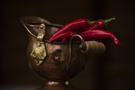 Pepper bitter, fresh in old, bronze ware, on a dark background