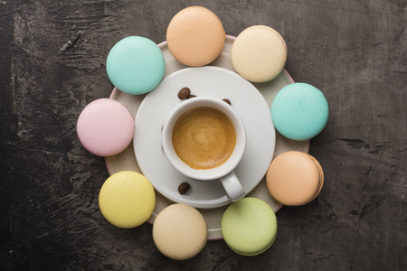 Fragrant coffee and colorful macaron cookies are arranged in a circle on a plate. Top view on a dark background