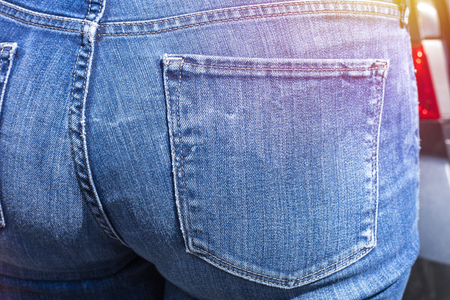 Close up of woman wearing blue jeans. Fit female butt in blue jeans