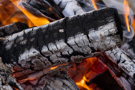 The texture of firewood in the flame. Consequences after a fire