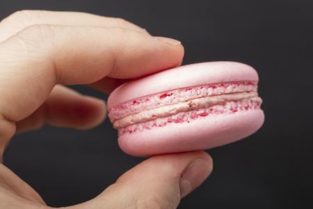 Pink macaron cookies in hand. Dark background
