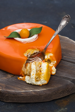 Orange cake in a mirror glaze, on a wooden tray