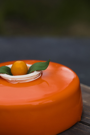 Orange cake in a mirror glaze, on a wooden tray