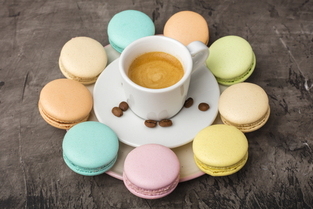 Fragrant coffee and colorful macaron cookies are arranged in a circle on a plate. Against a dark background