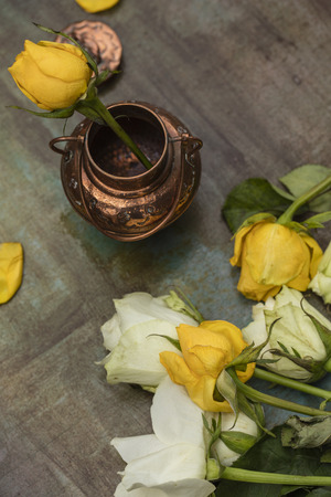 Yellow rose in a bronze vase, on a painted table, after a rain