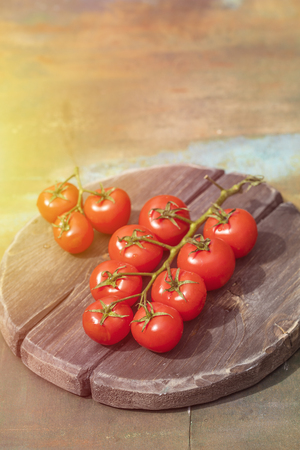 Ripe tomato branch on a wooden table, close-up. Water drops Imagens