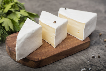Three soft cheeses with white mold on a wooden cutting board