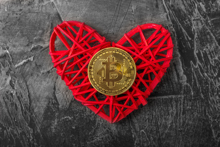 Love to bitcoins. Coin Bitcoin lies on a red heart, against a dark background
