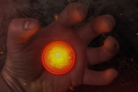 The hot coin Bitcoin lies on his hand. Hot money