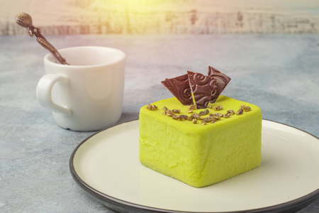 Pistachio pistachio, decorated with chocolate slices, on a plate with a tea cup on a light background