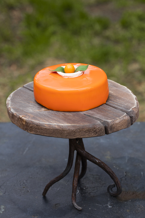 Cake with orange mousse and almond krokantom in the mirror glaze, on a wooden tray