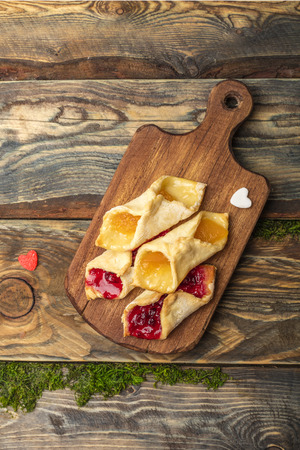 Homemade cookies with jam, on a cutting board. Wooden background