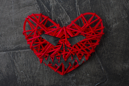 Red heart in the form of an evil head, a stone background