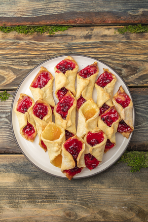 Homemade cookies with jam, on a plate. Wooden background. View from above