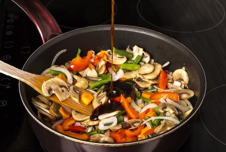 Aggiunta di salsa alle verdure fritte con funghi in una padella su uno sfondo scuro Archivio Fotografico