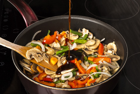 Agregar salsa a las verduras fritas con champiñones en una sartén sobre un fondo oscuro Foto de archivo