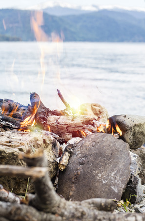 Campfire on the shore of Lake Teletskoye against the backdrop of the Altai mountains with a copy of the space