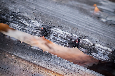Ashes of burned wood plank board damaged by of fire