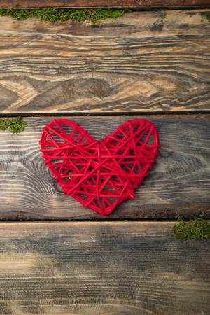 Red heart on a wooden board, wooden background. Copy space for your text