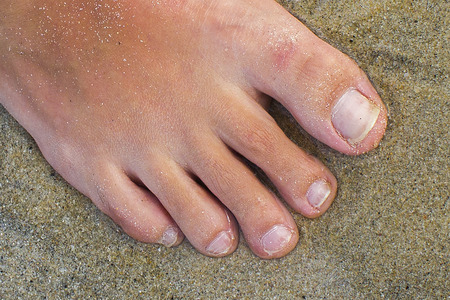 Female foot with a close-up on the sand. Pedicure