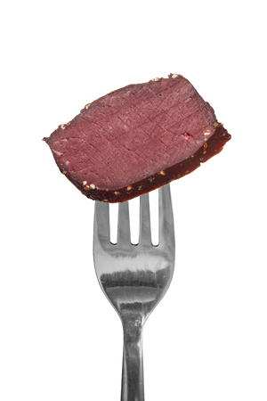 Venison meats from a venison on a fork, white background. Isolated object