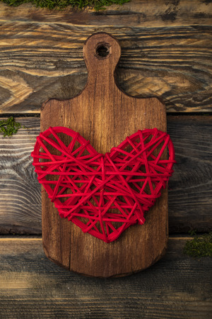 Big red heart on a wooden cutting board, wooden background. Copy space for your text