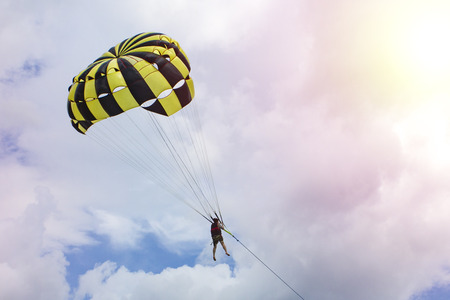 ourists fly by parachute with a boat. A man is flying on a yellow and black parachute in the sky. Copy space for your text