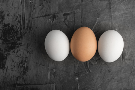 Three eggs, two white and one brown on a black background. Copy space 스톡 콘텐츠