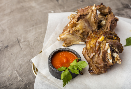 Roasted lamb meat on food paper with tomato sauce. Copy space