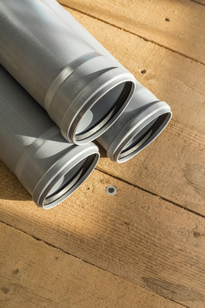 Gray PVC sewer pipes on a wooden floor background. Copy space
