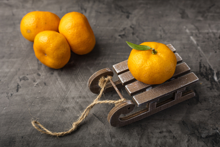 Christmas holiday concept, tangerine with leaf on wooden sledge on dark background
