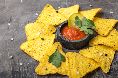 Tortilla Corn Chips or Nachos with sauce in a black bowl, on a dark background. Copy space