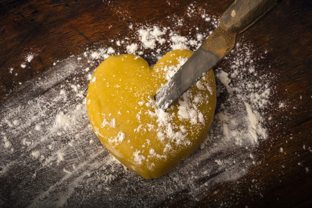 Knife into the heart, made of cookie dough on a rustic wooden background with the dusting of flour. Copy space. Background