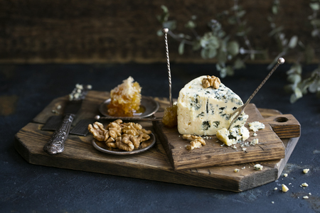 Danish blue cheese on a wooden board with walnut kernels. Copy space