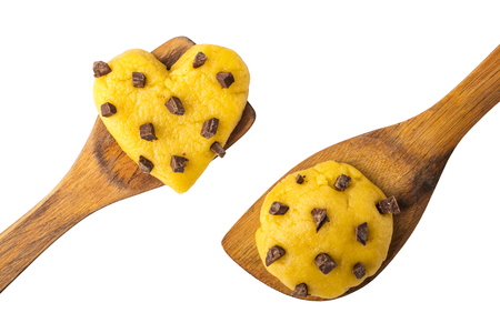 Raw cookie dough with chocolate chips in the shape of a heart and a circle on a wooden paddle. Isolated object Stock Photo
