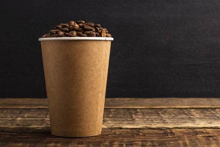 Disposable crafting cup with coffee grains on a wooden table with copy space. Black background. mockup Stockfoto