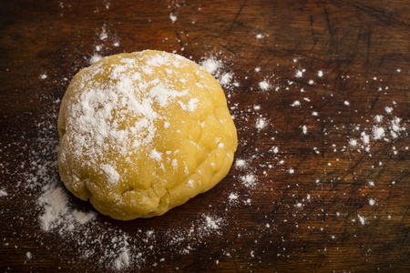 ball of dough sprinkled with flour on a wooden cutting board, copy space