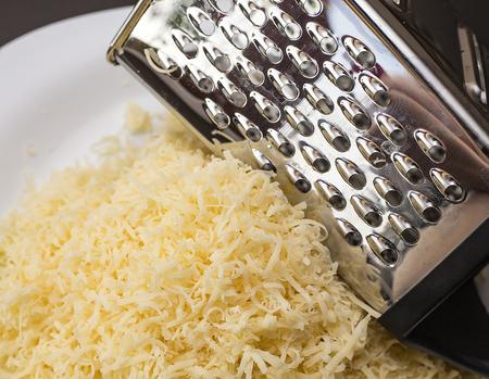 formaggio grattugiato e grattugia per verdure su un piatto. il formaggio si usa nella pasta, nelle zuppe, nei risotti e nelle insalate grattugiate Archivio Fotografico
