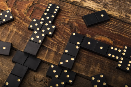 Playing dominoes on a wooden table. Domino effect. Copy space